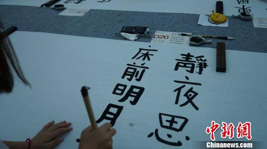 图为中日韩青少年正在用毛笔书写唐诗。 党田野 摄